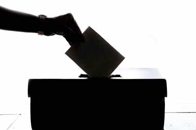Wahlzettel wird in Wahlurne gesteckt